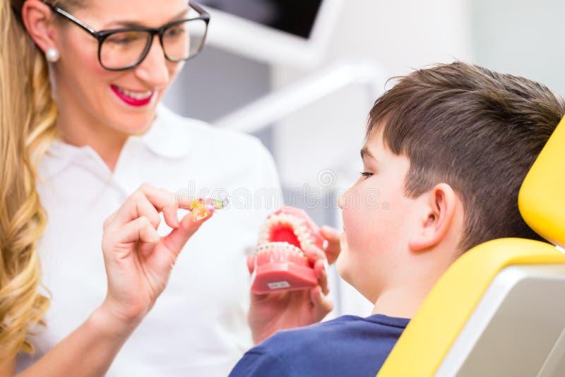 Menino de explicação do Orthodontist fêmea fotografia de stock