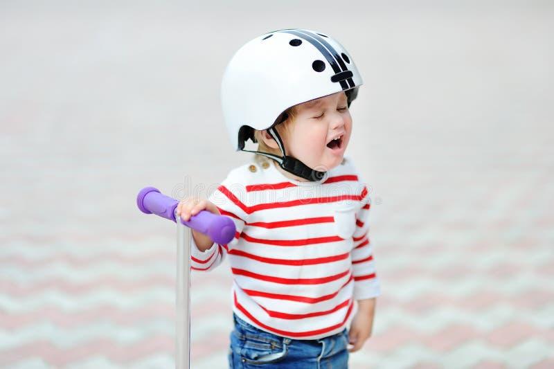 Menino de grito da criança no capacete de segurança com 'trotinette' imagem de stock royalty free