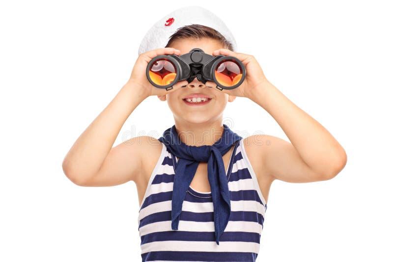 Menino de marinheiro pequeno que olha através dos binóculos isolados em b branco imagem de stock