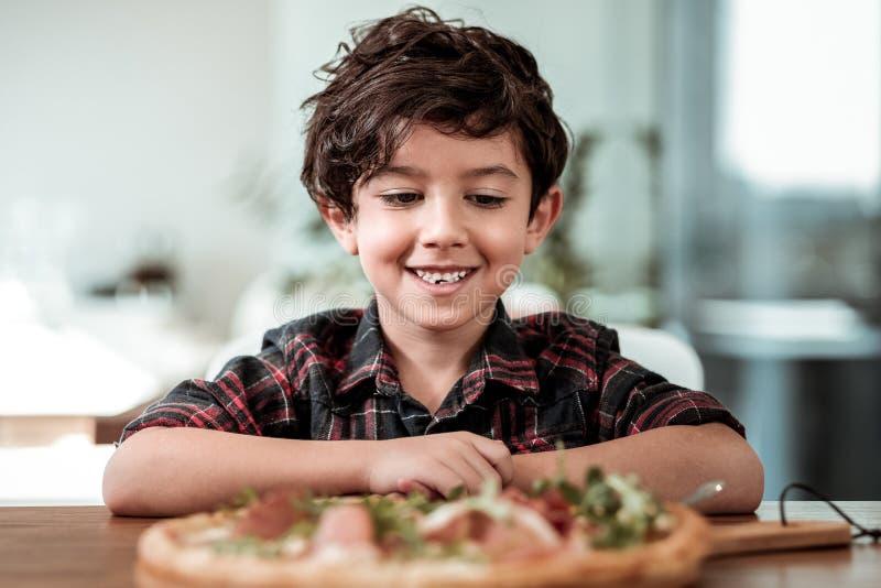 Menino de olhos escuros que senta-se na tabela com pizza com bacon e queijo foto de stock