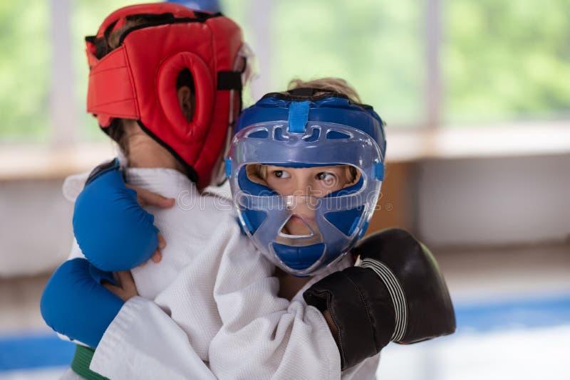 Menino de olhos escuros que veste o capacete protetor que luta com amigo imagem de stock