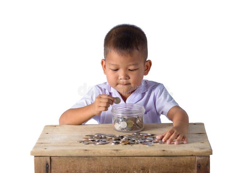 Menino de pa?s asi?tico bonito que p?e moedas na bacia de vidro isolada sobre o fundo branco imagem de stock
