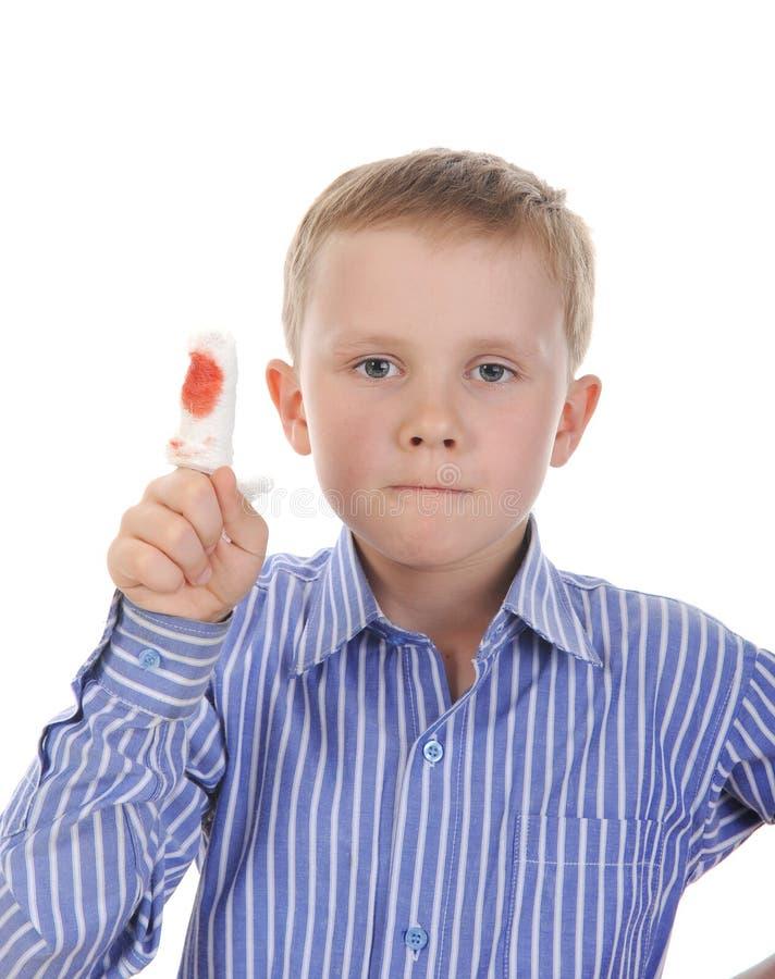 Menino de sete anos com um dedo enfaixado. foto de stock royalty free