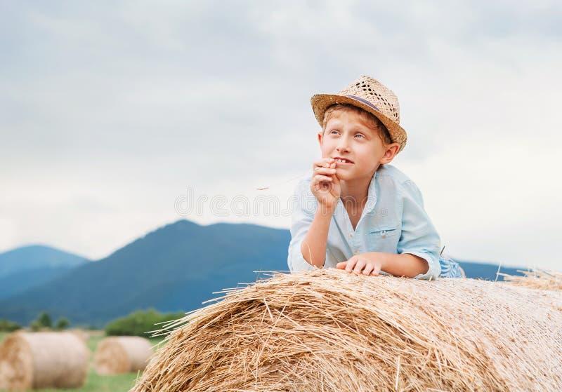 Menino de sonho que encontra-se no monte de feno do rolamento foto de stock royalty free