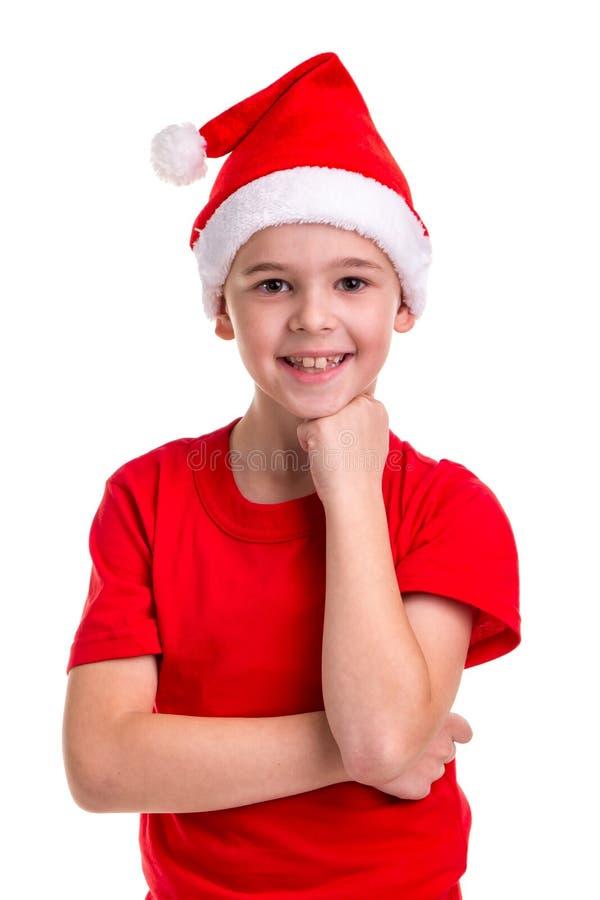 Menino de sorriso bonito, chapéu de Santa em sua cabeça, com o braço sob o queixo Conceito: Natal ou feriado do ano novo feliz imagem de stock