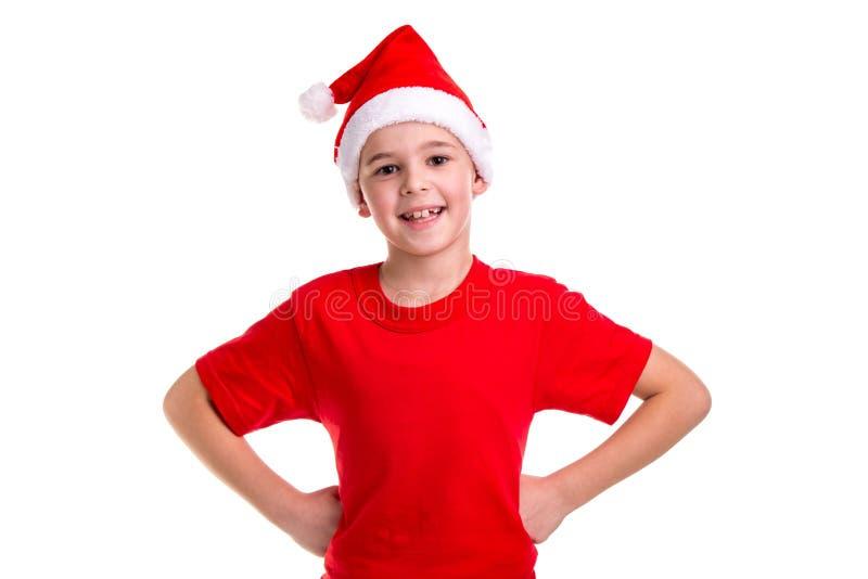 Menino de sorriso bonito, chapéu de Santa em sua cabeça, com os braços no conceito da cintura: Natal ou feriado do ano novo feliz fotografia de stock royalty free