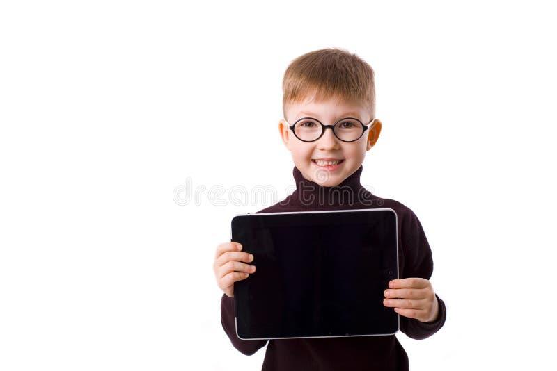 Menino de sorriso bonito de cinco anos com uma tabuleta nas mãos fotos de stock royalty free