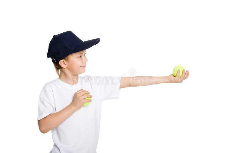 Menino de sorriso com esferas de tênis imagem de stock royalty free