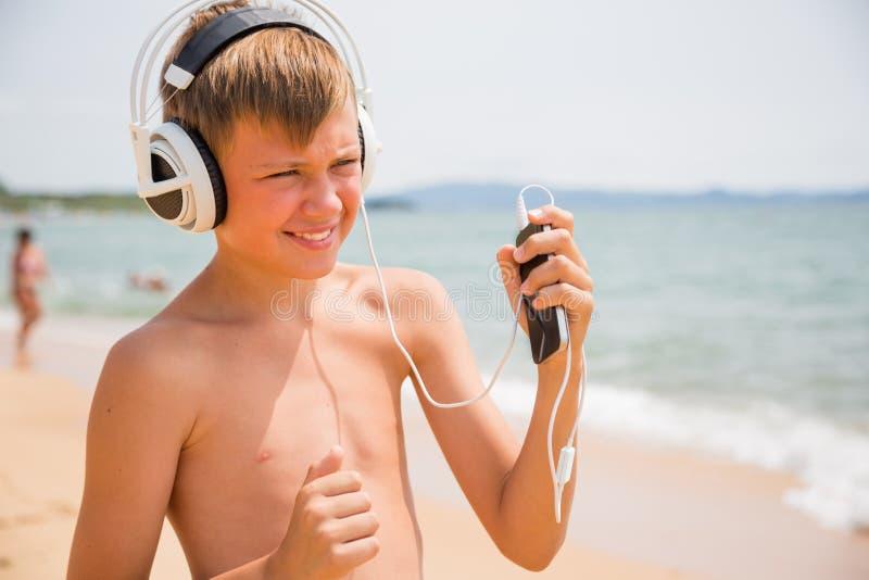 Menino de sorriso com fones de ouvido usando um smartphone imagem de stock