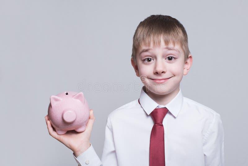 Menino de sorriso com o porco cor-de-rosa do mealheiro em suas m?os Conceito do neg?cio Fundo claro fotos de stock