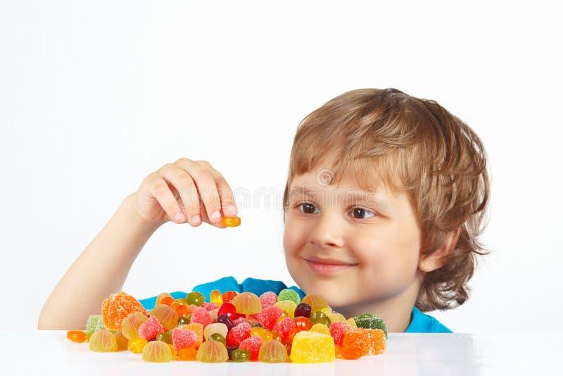 Menino de sorriso com os doces coloridos da geleia no fundo branco imagens de stock royalty free