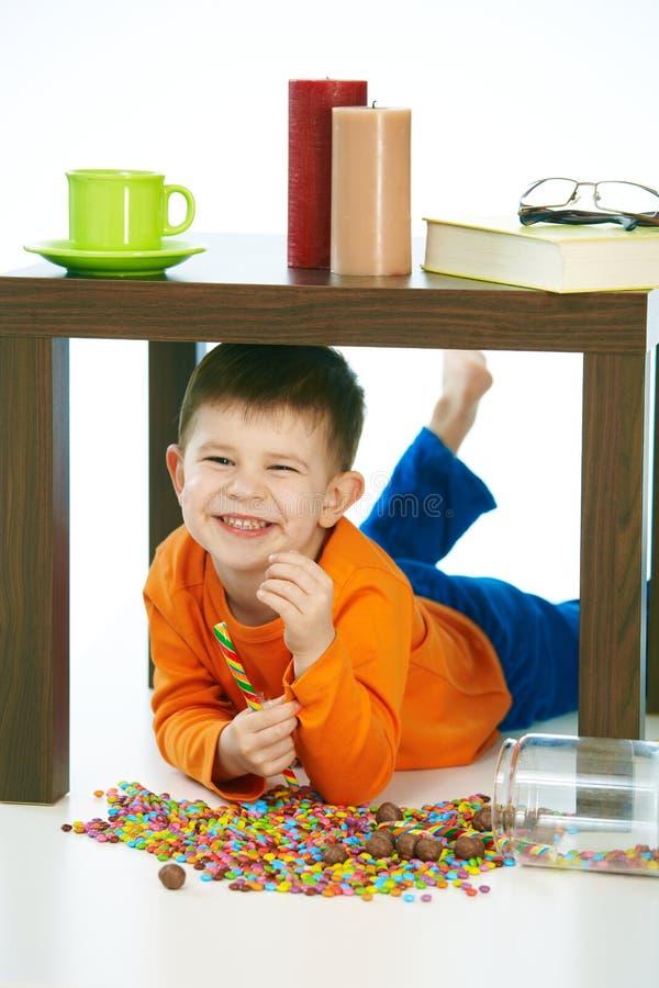 Menino de sorriso com os doces sob a tabela em casa interna imagens de stock royalty free