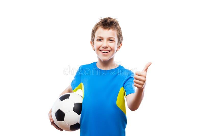 Menino de sorriso considerável da criança que guarda a bola de futebol que gesticula o polegar acima do sinal do sucesso imagens de stock royalty free