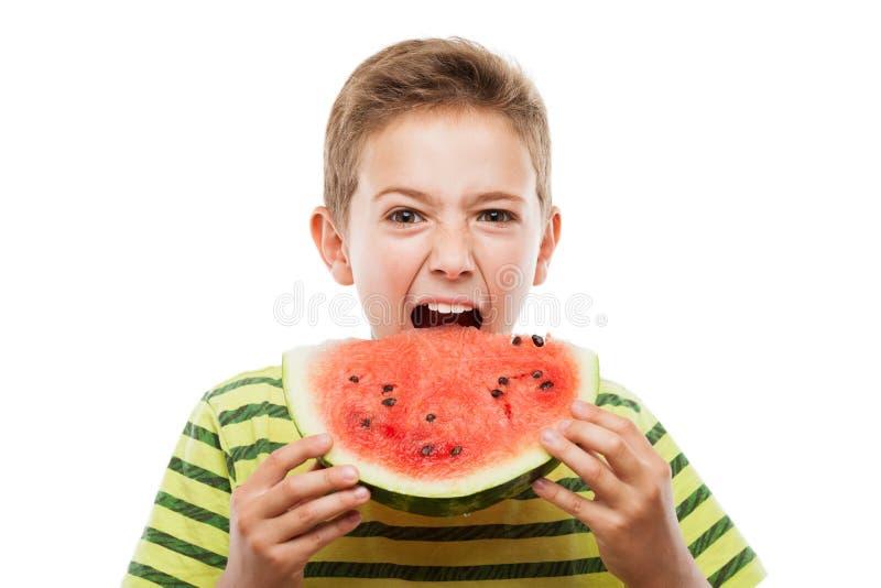 Menino de sorriso considerável da criança que guarda a fatia vermelha do fruto da melancia foto de stock