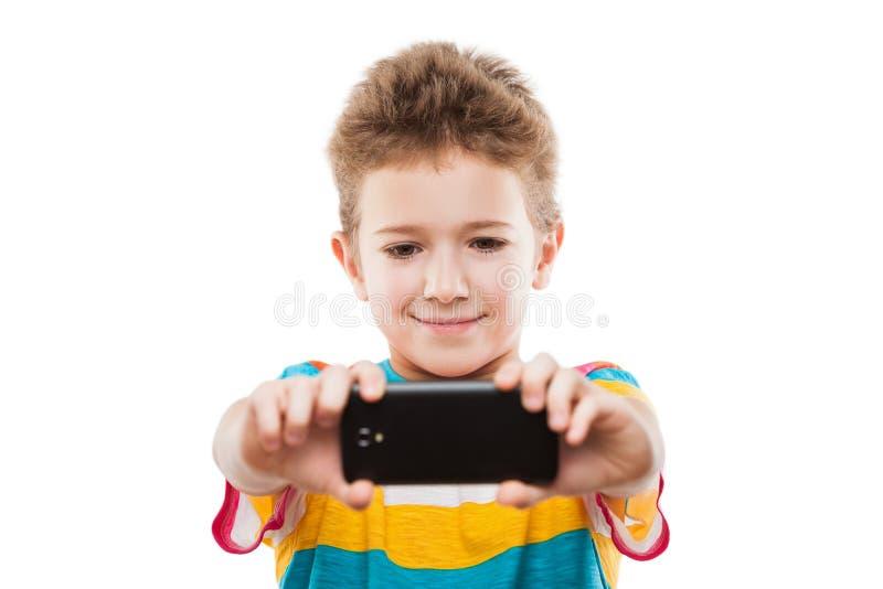 Menino de sorriso da criança que mantém o telefone celular ou o smartphone que tomam o auto imagens de stock
