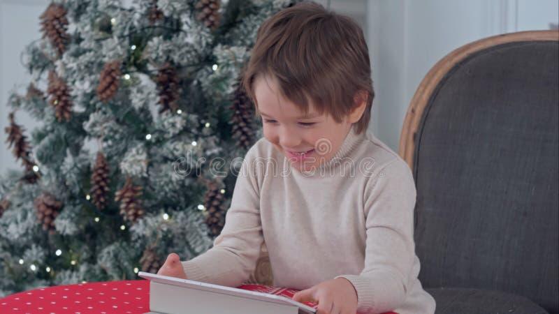 Menino de sorriso da criança que senta-se em uma cadeira e que joga com a tabuleta durante o tempo do Natal imagem de stock royalty free