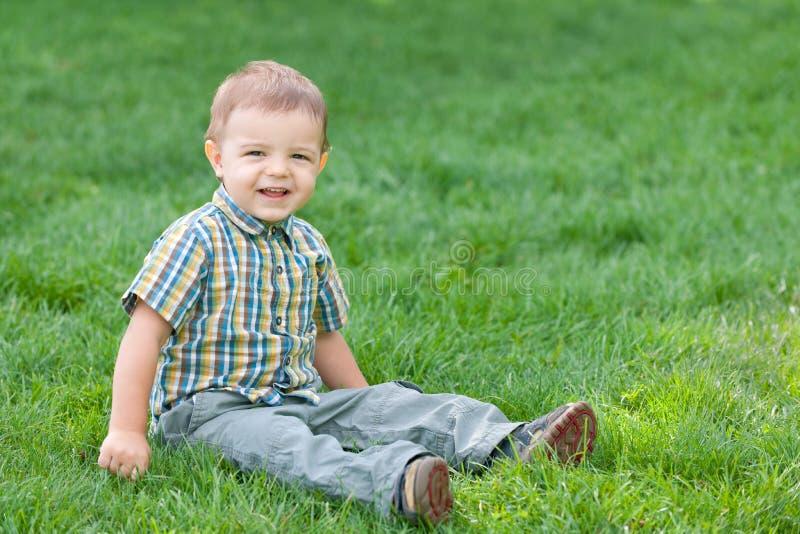 Menino de sorriso de encontro à grama verde do verão fotos de stock royalty free