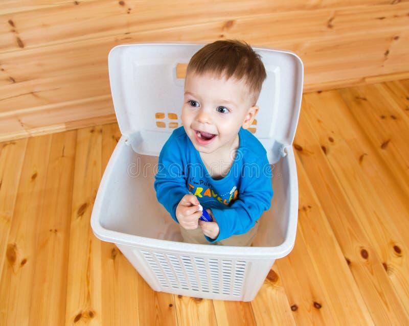Menino de sorriso do bebê de um ano que sai da lata de lixo imagens de stock royalty free