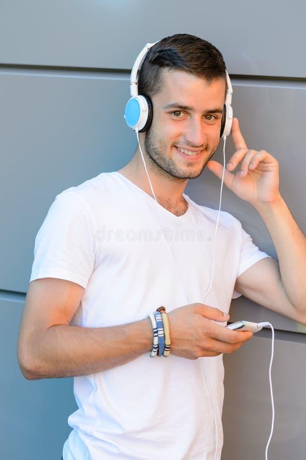 Menino de sorriso do estudante com os fones de ouvido contra a parede fotografia de stock royalty free