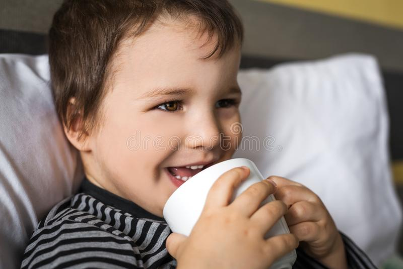 Menino de sorriso doente da criança que toma o copo do medicamento que encontra-se na cama imagem de stock royalty free