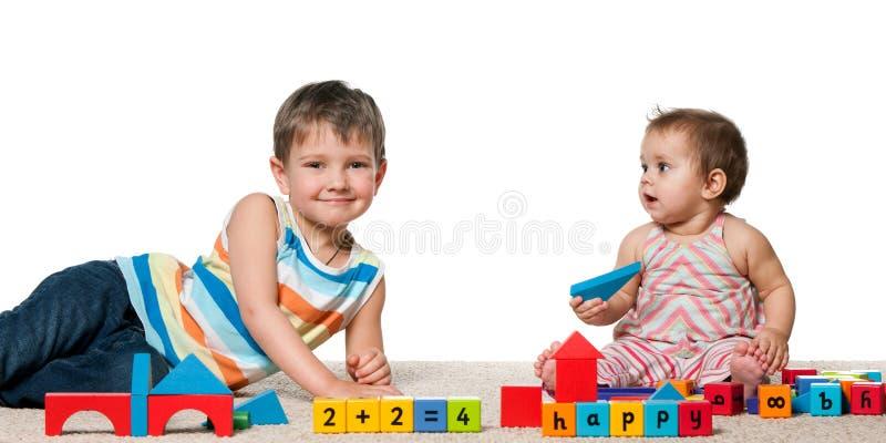Menino de sorriso e um bebé com blocos fotografia de stock