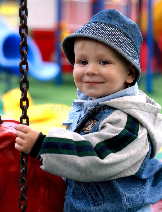 Menino de sorriso em um merry-go-round imagens de stock