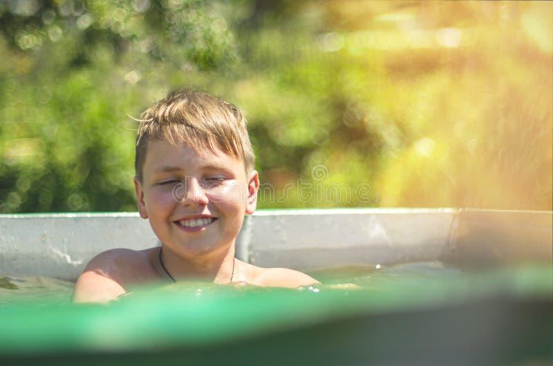 Menino de sorriso feliz que espirra em uma piscina em Sunny Summer Day quente Raios de sol, alargamento morno de Sun Fundo verde  foto de stock royalty free