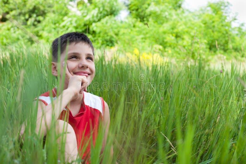 Menino de sorriso na grama verde foto de stock