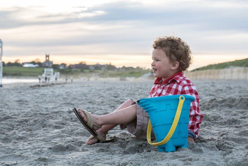 Menino de sorriso na praia com o balde azul no por do sol foto de stock