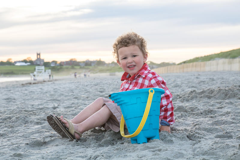 Menino de sorriso na praia com o balde azul no por do sol fotografia de stock