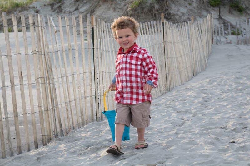 Menino de sorriso na praia com o balde azul no por do sol imagens de stock