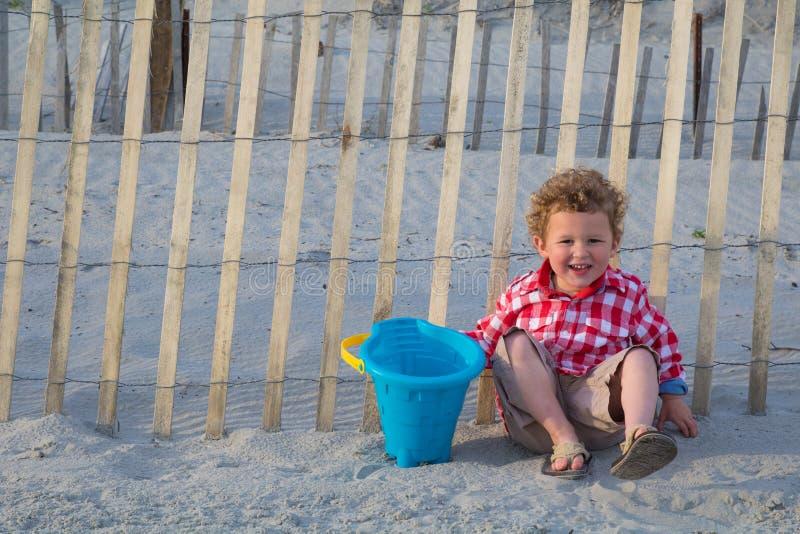 Menino de sorriso na praia na frente da cerca de madeira foto de stock