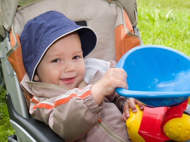 Menino de sorriso no carrinho de criança fotografia de stock