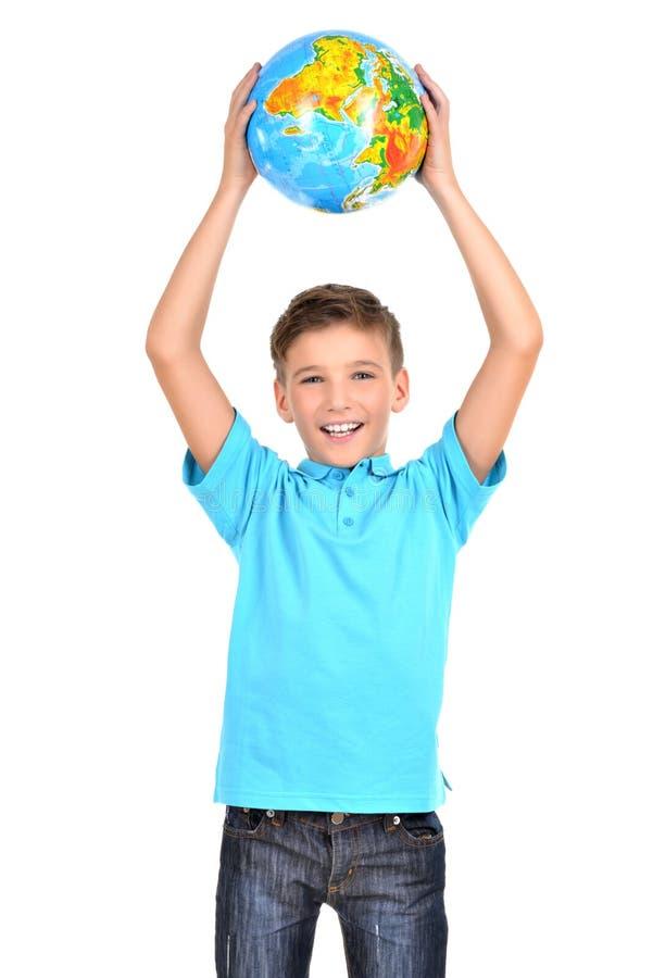 Menino de sorriso no globo guardando ocasional nas mãos acima de sua cabeça fotografia de stock royalty free