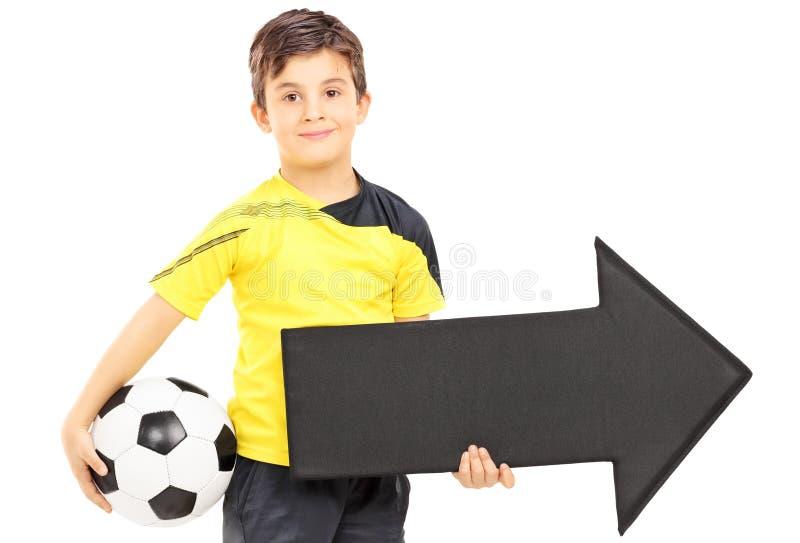 Menino de sorriso no sportswear que guarda um pointi da bola e da seta de futebol foto de stock