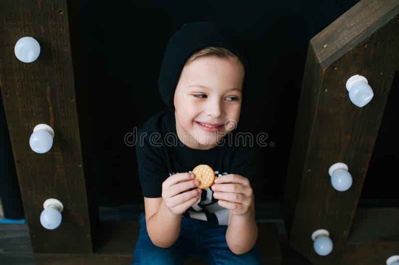 Menino de sorriso novo que come a cookie closeup imagem de stock