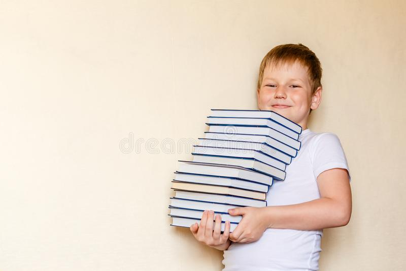 Menino de sorriso de oito anos que guarda muitos livros Primeiro-graduador foto de stock