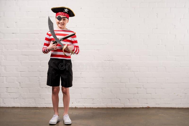 menino de sorriso pequeno com faca e arma do brinquedo no pirata imagens de stock