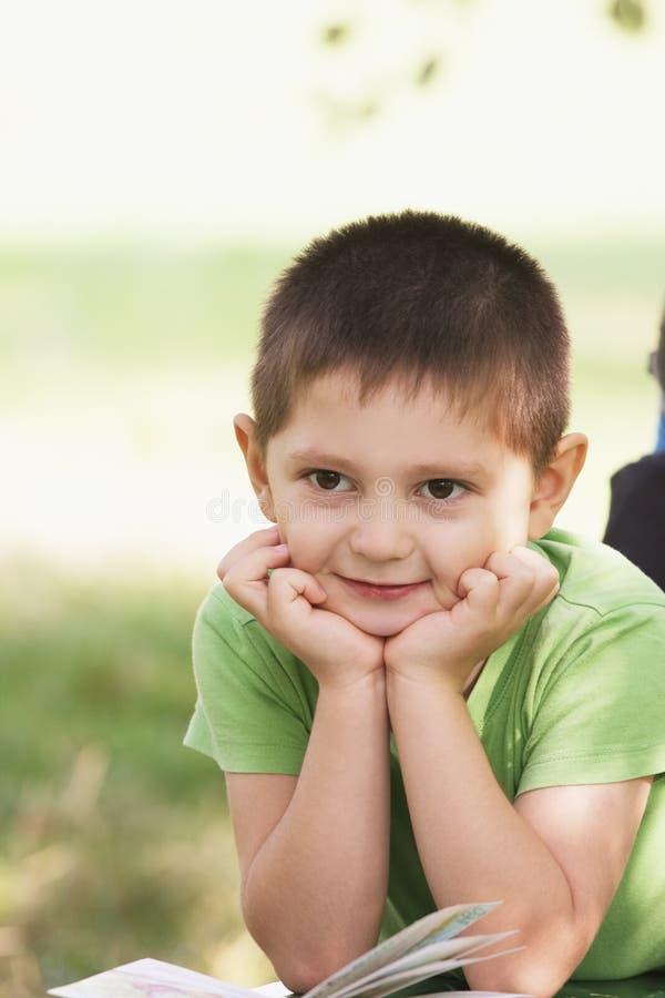 Menino de sorriso pequeno com o livro no parque fotos de stock royalty free