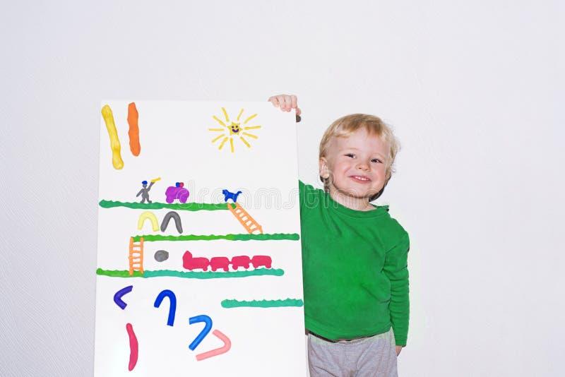 Menino de sorriso pequeno com placa da argila do jogo foto de stock