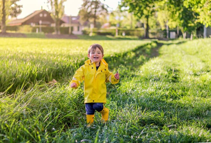 Menino de sorriso pequeno feliz na capa de chuva amarela brilhante e nas botas de borracha que correm através do campo com grama  foto de stock