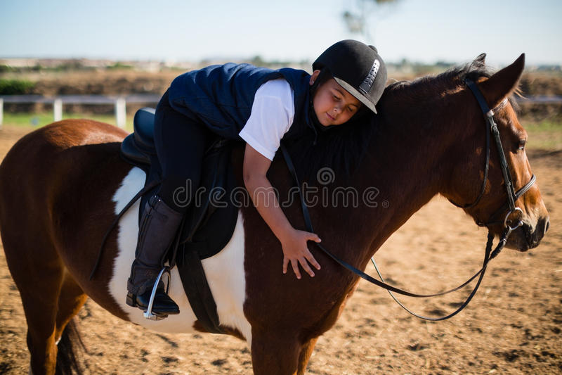 Menino de sorriso que abraça o cavalo branco no rancho imagens de stock