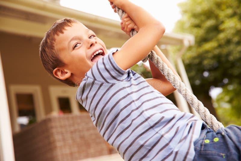 Menino de sorriso que balança em uma corda em um campo de jogos fotografia de stock