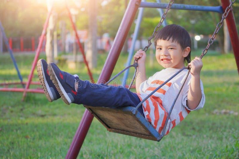 Menino de sorriso que balança em uma corda em um campo de jogos imagem de stock