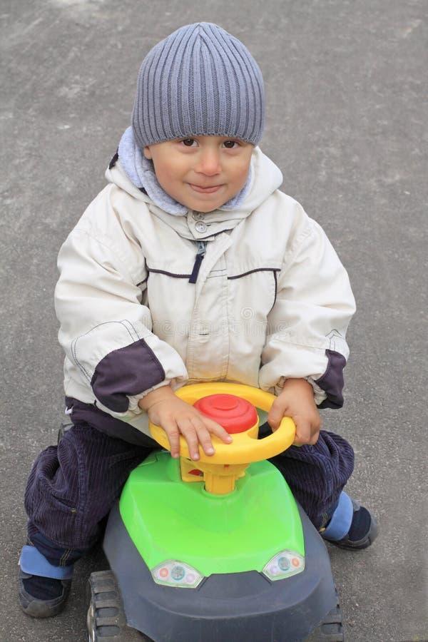 Menino de sorriso que conduz o carro do brinquedo imagens de stock royalty free