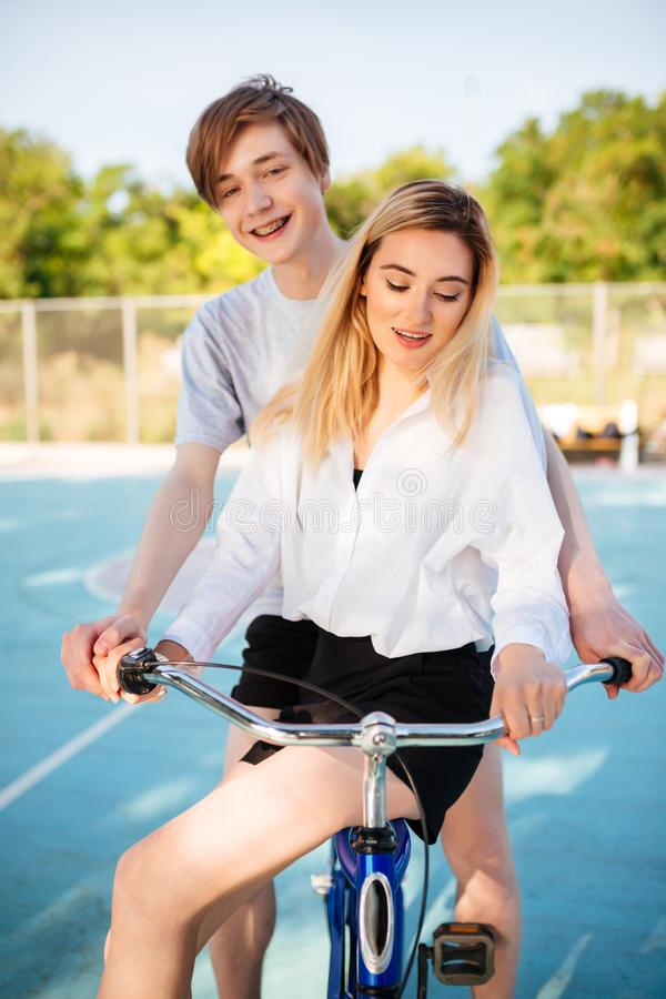 Menino de sorriso que olha felizmente in camera ao montar na bicicleta com a menina bonita no campo de básquete Pares bonitos nov imagem de stock royalty free