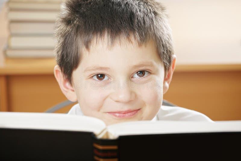 Menino de sorriso que olha sobre o livro fotos de stock royalty free