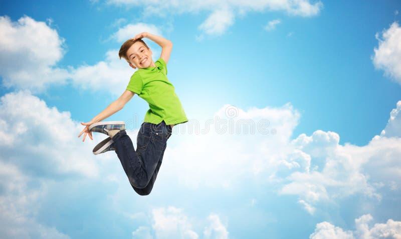 Menino de sorriso que salta no ar fotos de stock