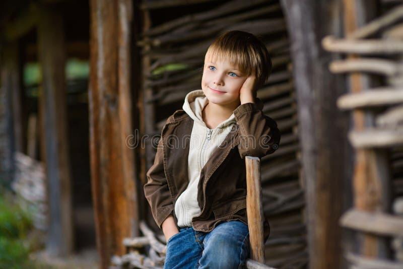 Menino de sorriso que senta-se na cerca no jardim foto de stock royalty free