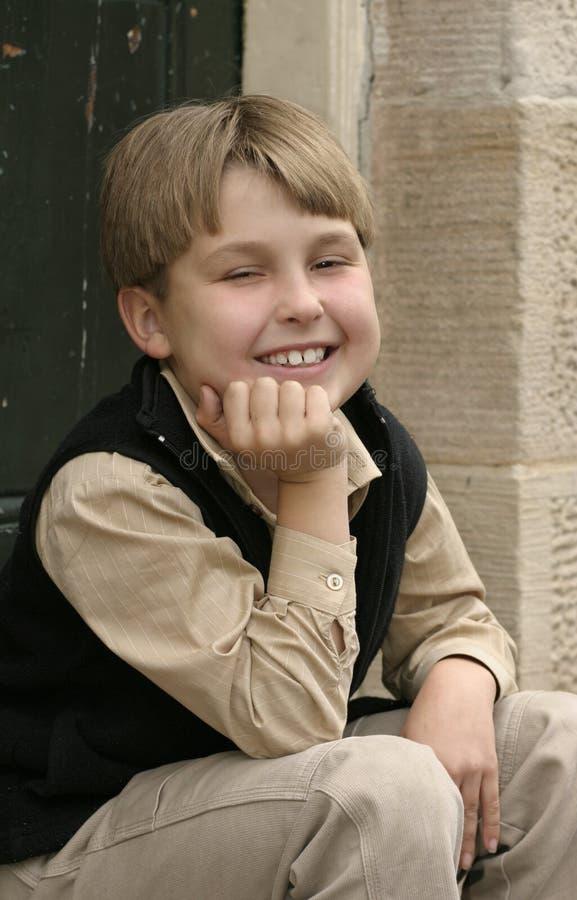 Menino de sorriso que senta-se na entrada imagens de stock
